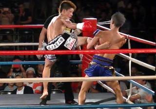 ジャンプしてのミドルを見舞う佐々木(左)、その蹴り足をキャッチする伊藤(右)。本場タイでも試合をしている両者のテクニックが存分に発揮された