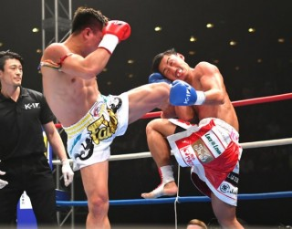 ゴンナパー(左)の強烈な左ミドルに身体ごともっていかれ、顔が苦痛に歪む山崎(右)